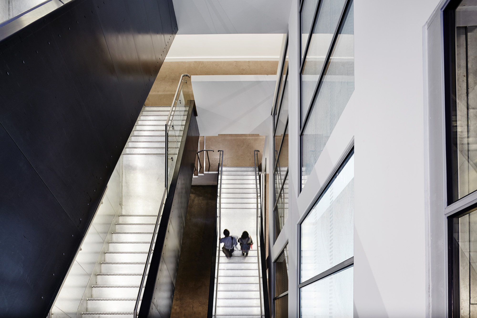 Two students walk down the stairs inside Guntons building