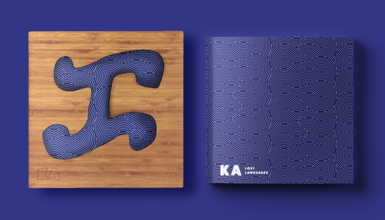 MA Communication Design work by Camille Cabiscuelas showing a cover design for KA, image shows a cover with wooden texture background and a blue graphic with intricate white detail and another cover a dark blue with intricate white detail and 'KA' in the bottom left hand corner.