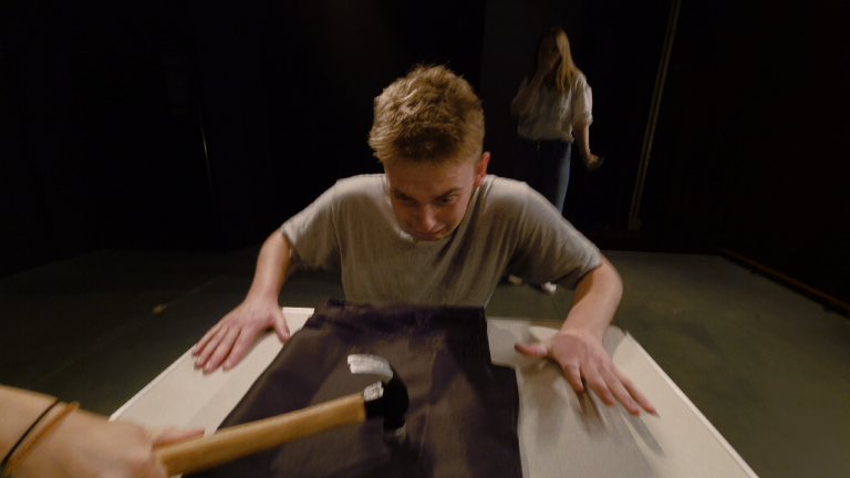 Still from a short film – a hammer crashes down on a table before a horrified man, while a girl looks on in shock.