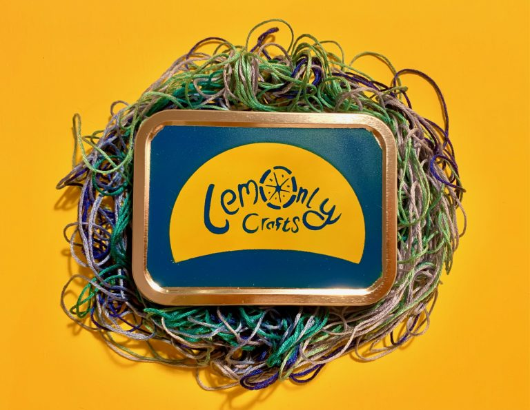 Colourful Tin surrounded by blue and green embroidery thread on a yellow background