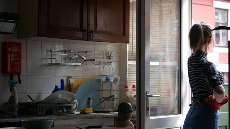 Photo by Jamie Marks. From inside a softly lit kitchen with a woman standing at the kitchen door staring out