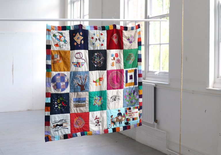 A brightly coloured modular patchwork quilt, shown hanging in a white studio space. Each patch of the quilt has a different stitched design, some are abstract, some are more figurative.