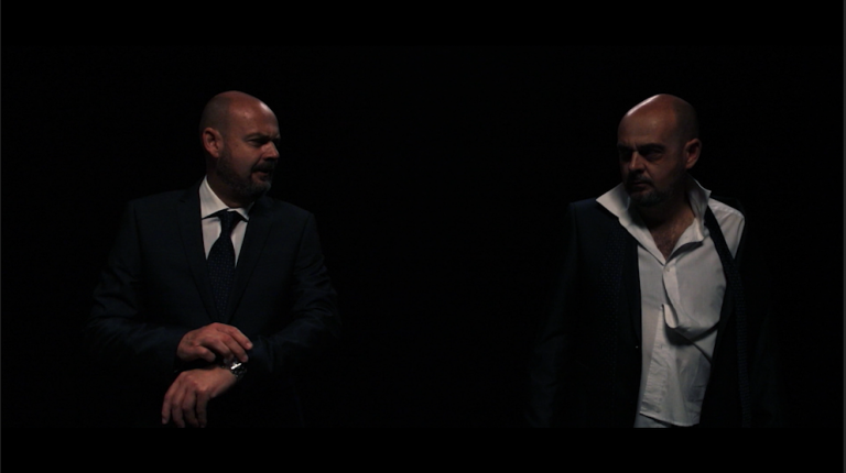 A still from my film showing two versions of the same man, one in a smart suit and the other looking disheveled.