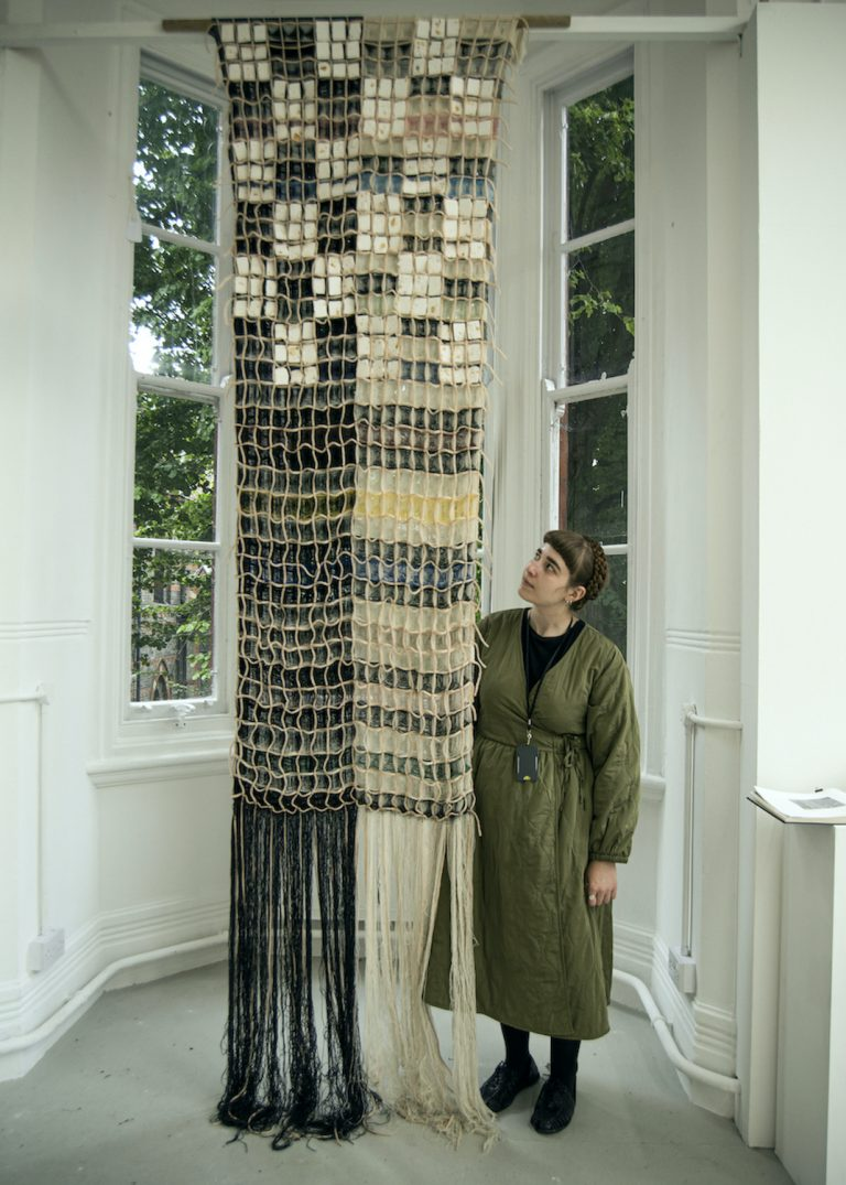 MA woven textiles by Megan Stavaru showcasing a large scale three-dimensional woven wall with colourful yarn and blocks of plaster embedded into the woven work