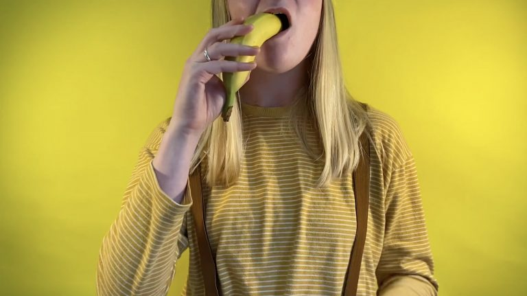 MA Communication Design artist Vicky Bass is dressed in all yellow against a yellow background. She is eating a banana with the skin on.