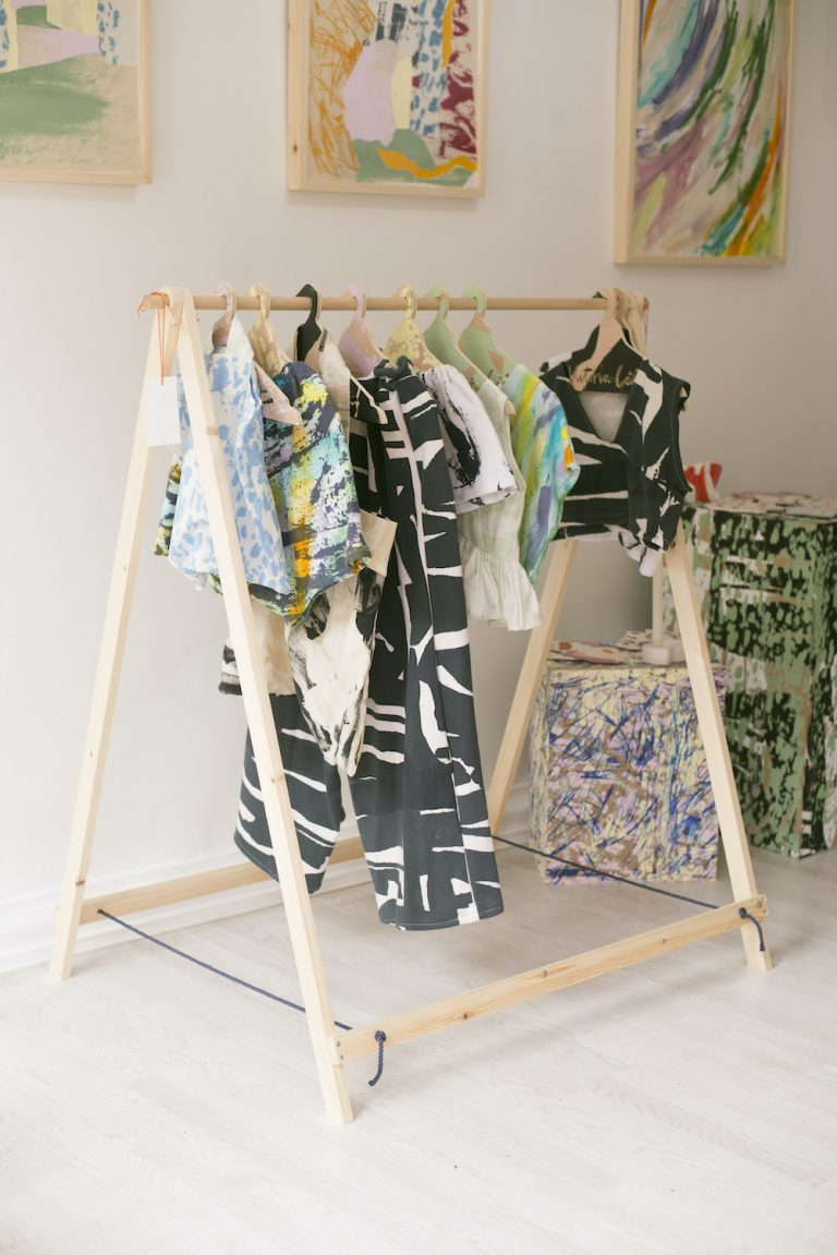 A rail of screen-printed garments on a rail in the concept store with collaged framed prints on the wall behind